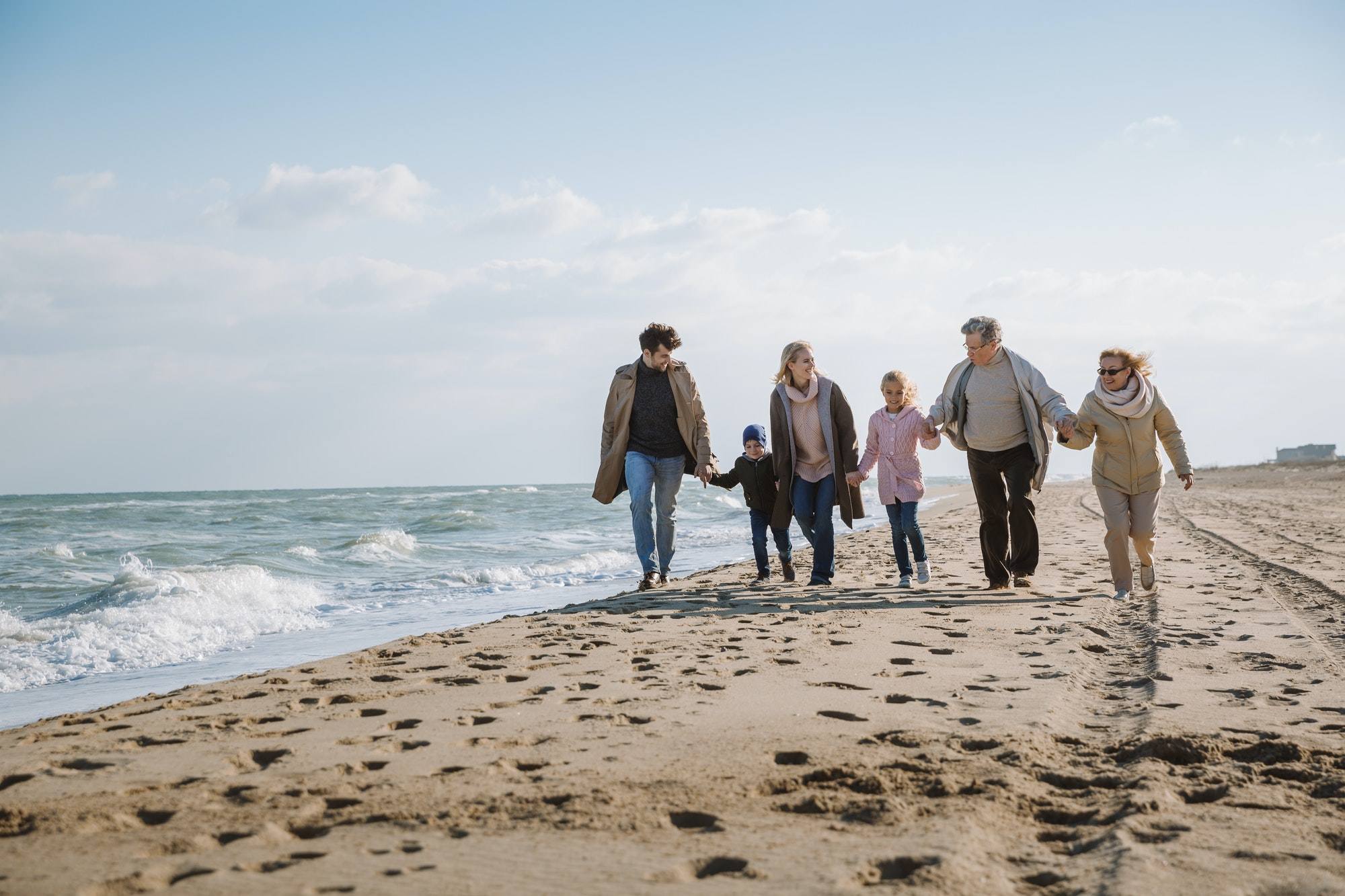 big multigenerational family walking together on beach at seaside