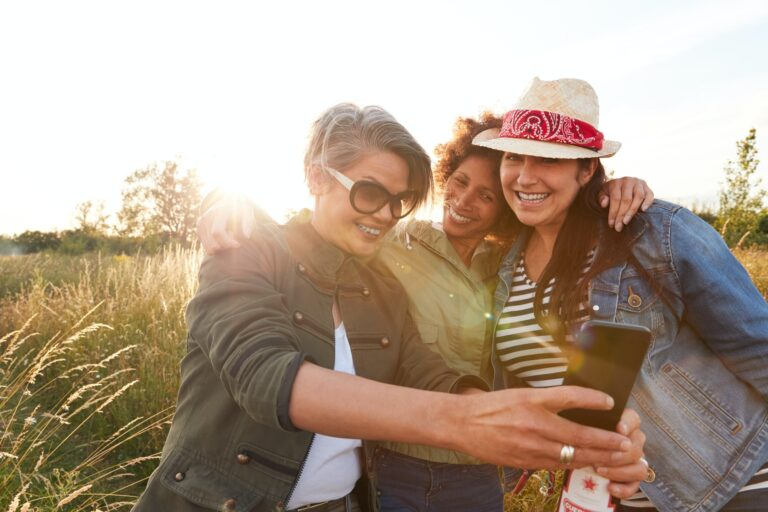 Group Of Mature Female Friends Walking Through Field On Camping Posing For Selfie