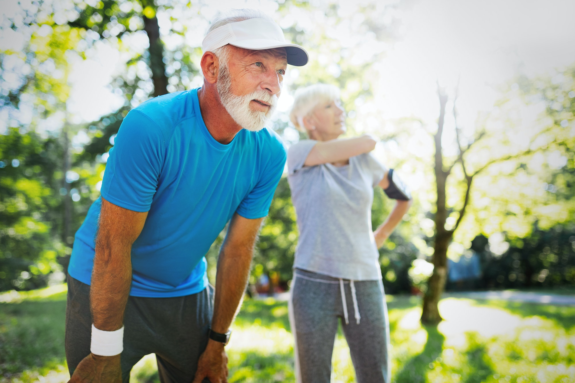 Mature couple jogging and running outdoors in nature