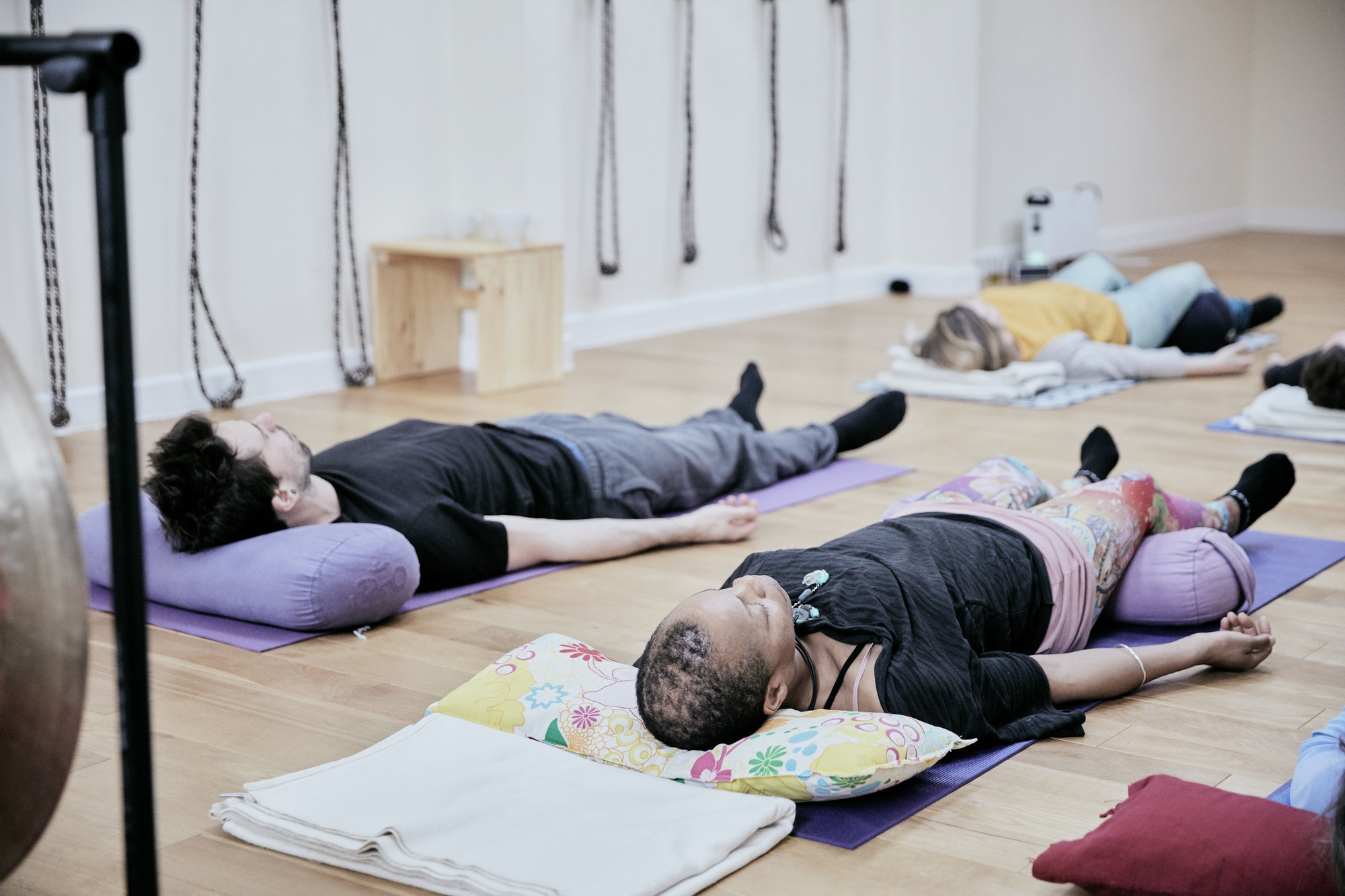 People lying down on an exercise studio floor relaxing after a sound therapy session