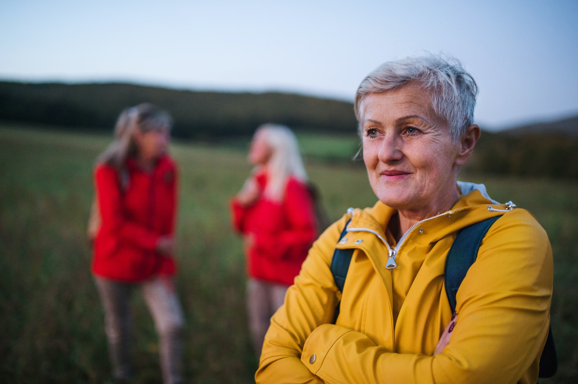 Senior women friends on walk outdoors in nature at dusk