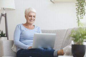 Smiling old woman typing email on laptop
