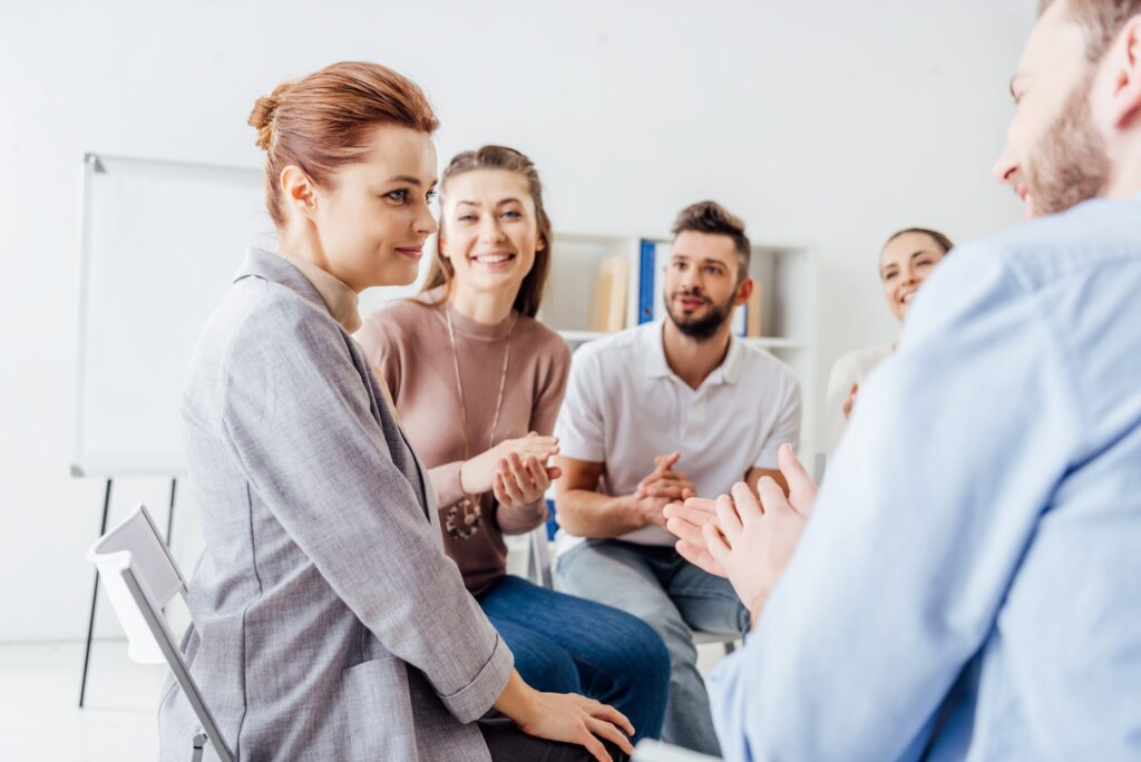 smiling people sitting and applauding during group therapy meeting