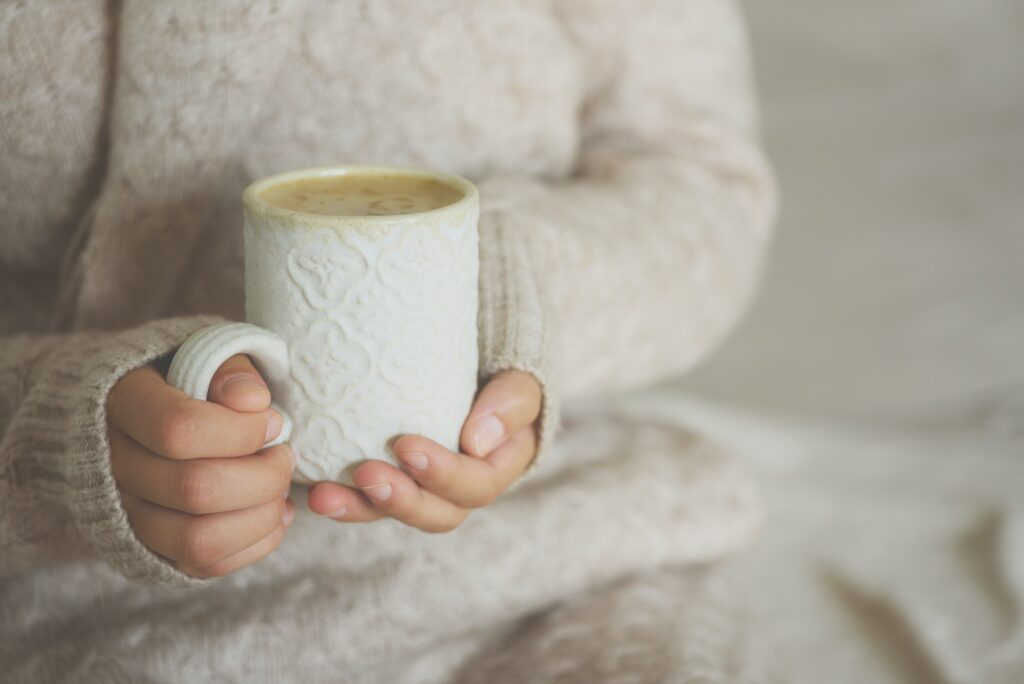 Famale hands holding a cozy ceramic handmade mug with coffe. Winter and Christmas home time concept