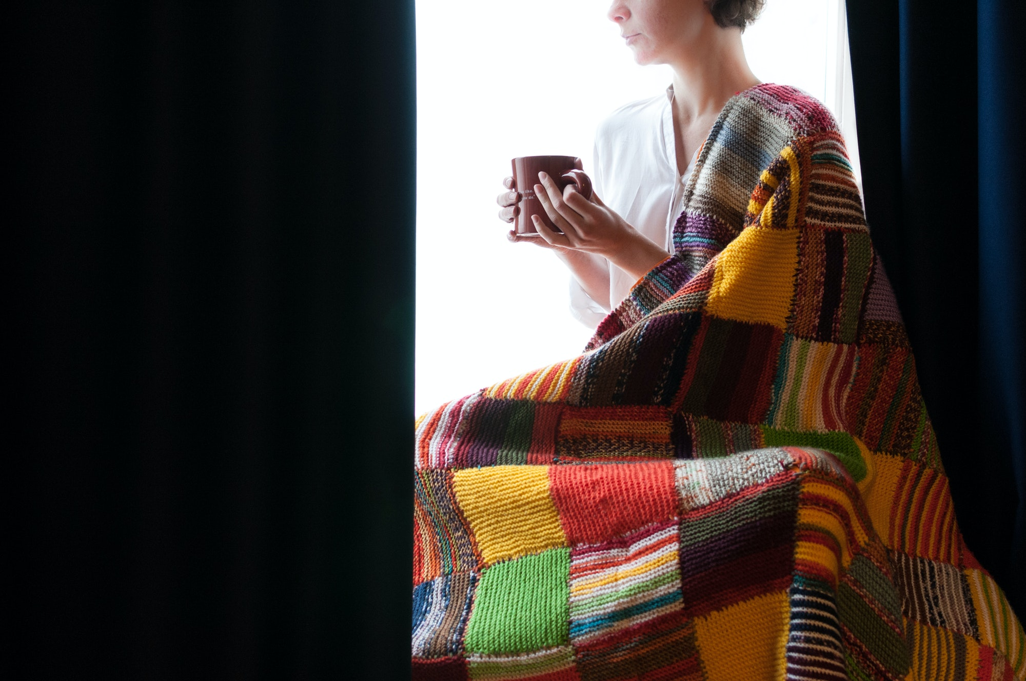 Girl is looking at the window with the cup of coffie