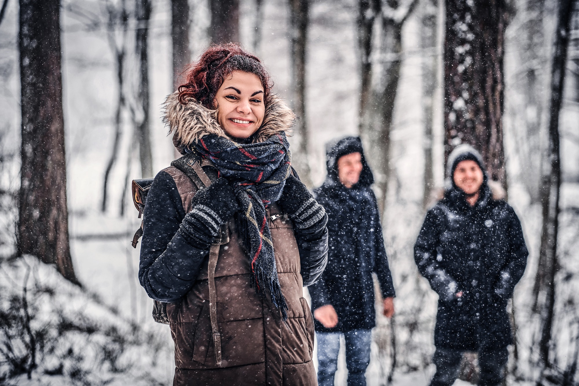 Redhead girl with friends walk in the winter in the woods