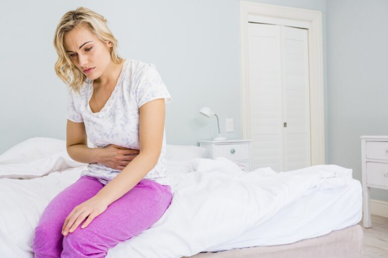 Young woman having stomach pain in bed