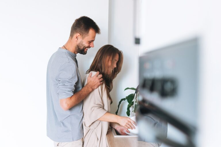 Happy young family couple in love washes dishes in bright modern kitchen