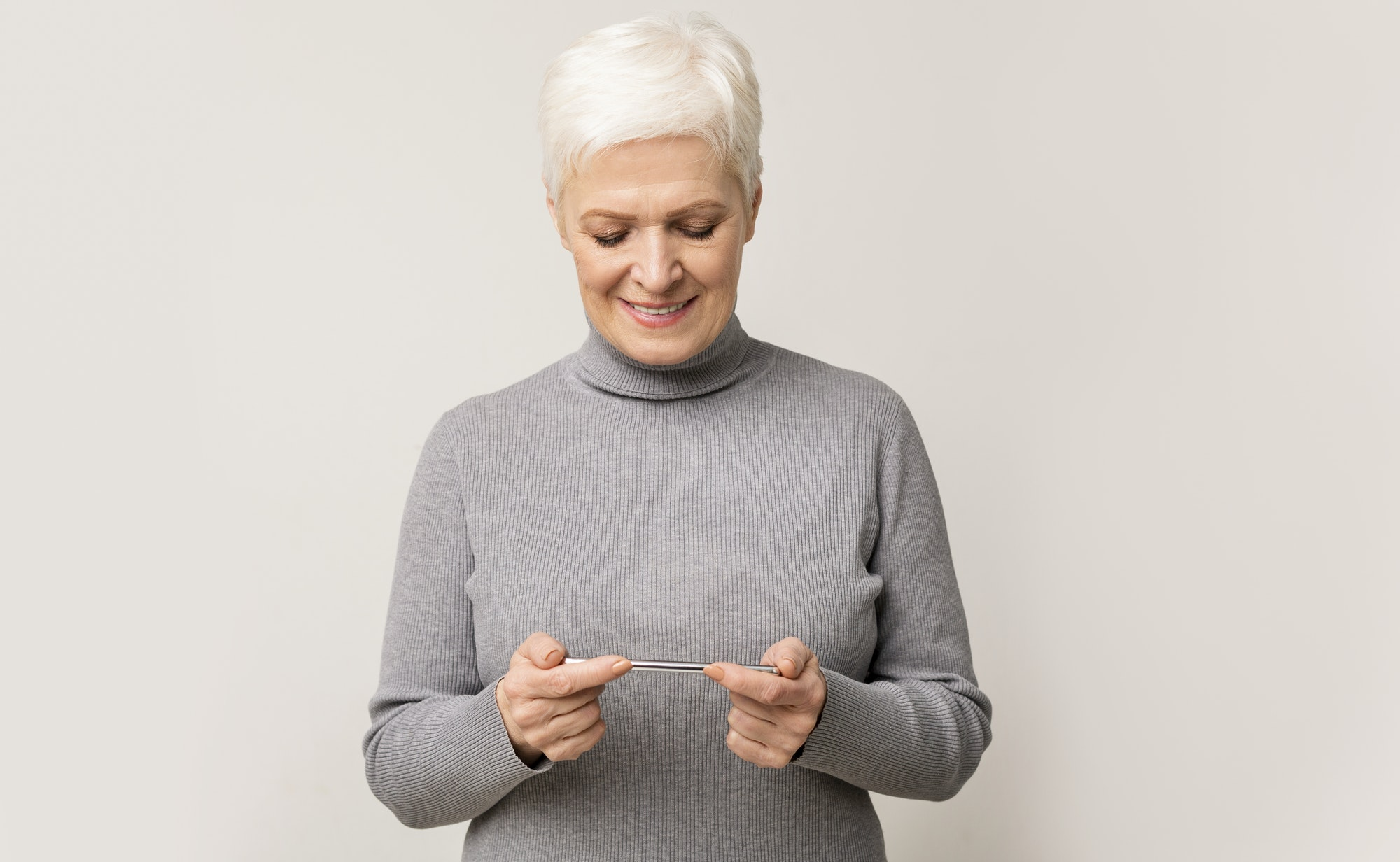Senior woman playing video game on mobile phone and smiling