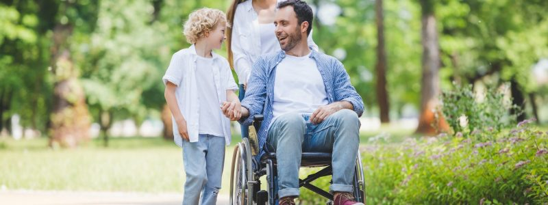 beautiful mother rolling wheelchair with disabled father in park near son
