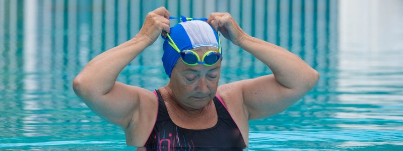 close up of one mature woman fixing her goggles in a swimming pool alone