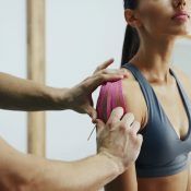 Doctor helps woman by shoulder treatment with kinesio tape