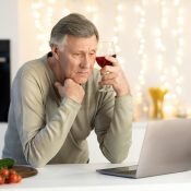 Lonely Elderly Man Celebrating Christmas Alone At Laptop In Kitchen