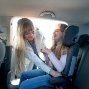 Mom helping her daughter to fasten belt in child car seat