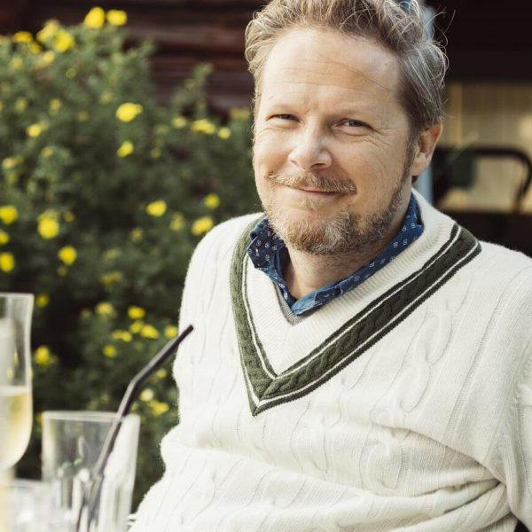 Portrait of mature man sitting at table in garden
