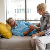Senior woman comforting man with depression, health problem, stress at home