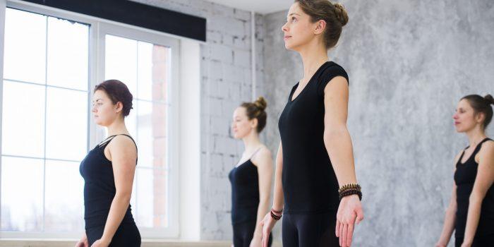 Women doing yoga sun salutation pose indoors at yoga studio